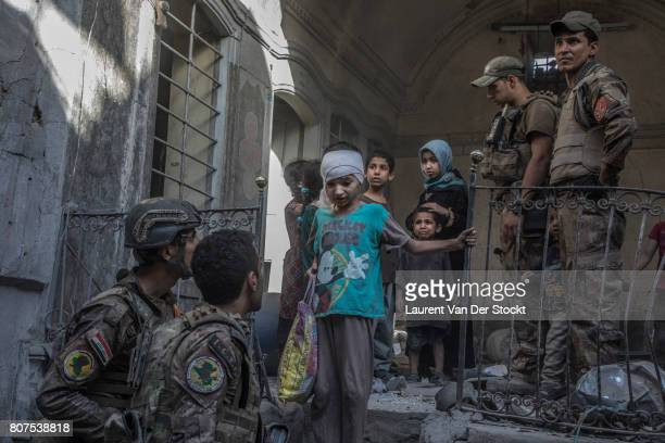 Iraqi soldiers evacuate a family they discovered in alNuri mosque complex on June 29 in Mosul Iraq The Iraqi Army Special Operations Forces and...