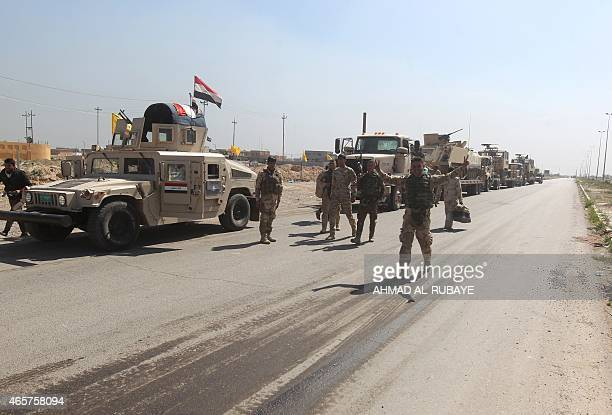 Iraqi soldiers flash the sign for victory on the outskirts of the city of Tikrit as they prepare to launch a military operation to take control of...