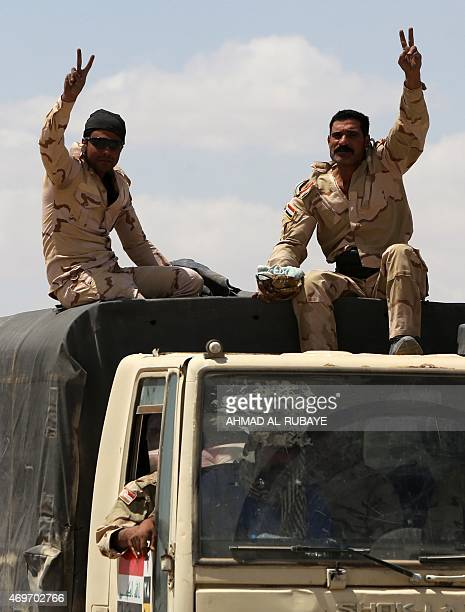 Iraqi soldiers flash the sign of victory on a military vehicle driving on April 14 2015 to the front line in the Garma district west of the Iraqi...