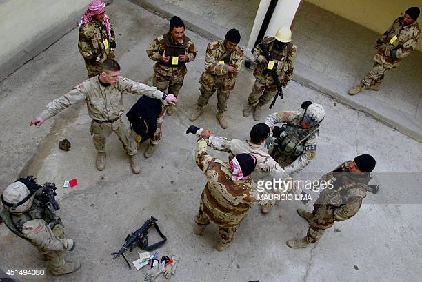 Iraqi soldiers frisk US soldiers from the 1st Battalion 24th Infantry Regiment as they receive a security training showing how they have to frisk...