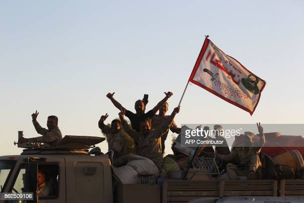Iraqi soldiers gesture on top of a vehicle as they enter the city of Kirkuk on October 17, 2017. Kurdish peshmerga forces withdrew without a fight...