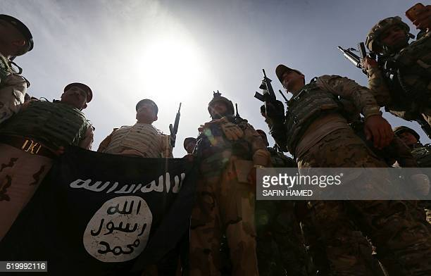 Iraqi soldiers hold a flag that they seized from the Islamic State group as they hold a position near the frontline on April 9 2016 in the town of...