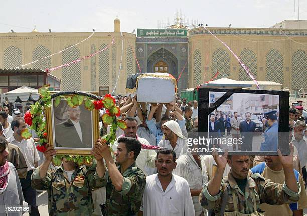 Iraqi soldiers hold pictures of alMuthana governor Mohammed Ali alHassani and his bodyguard during their funeral in Najaf 160 kms south of Baghdad 21...