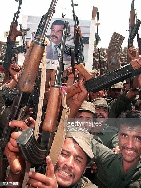 Iraqi soldiers hold up their arms during celebrations to mark the 61st birthday of Iraqi President Saddam Hussein 28 April 1988 in his home town of...