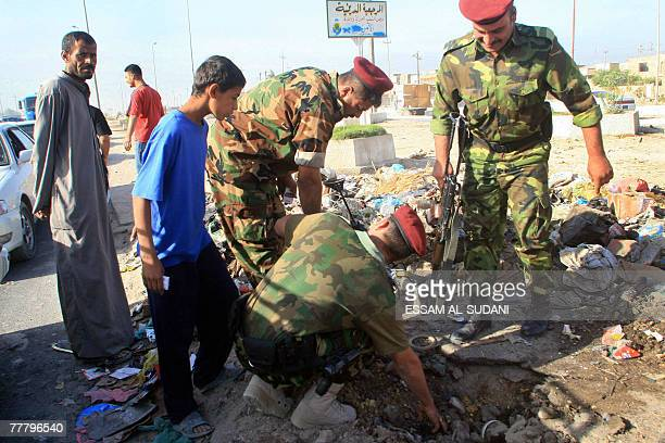 Iraqi soldiers inspect a crater left by the explosion of a roadside bomb in the southern city of Basra 08 November 2007 The blast targeted the city's...