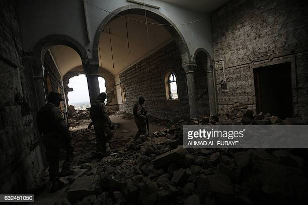 Iraqi soldiers inspect the debris on January 22 2017 at St George's Monastery a historical Chaldean Catholic church on the northern outskirt of Mosul...