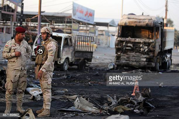 Iraqi soldiers inspect the site of a car bomb explosion at a checkpoint in the mostly Shiite Sadr City district of Baghdad on October 14 2014 The...