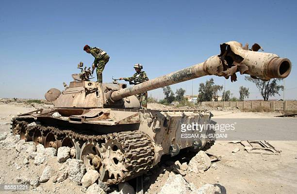 Iraqi soldiers inspect the wreckage of an old Iraqi tank destroyed during the 2003 US-led invasion in the southern city of Basra on March 22, 2009....