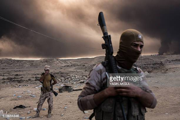 TOPSHOT Iraqi soldiers look on as smoke rises from the Qayyarah area some 60 kilometres south of Mosul on October 19 as Iraqi forces take part in an...
