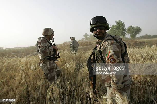 Iraqi soldiers of 1st Brigade, 3rd Battalion yell to their comrades next to a US soldier of 1st Battalion, 187th Infantry Regiment, 101st Airborne...