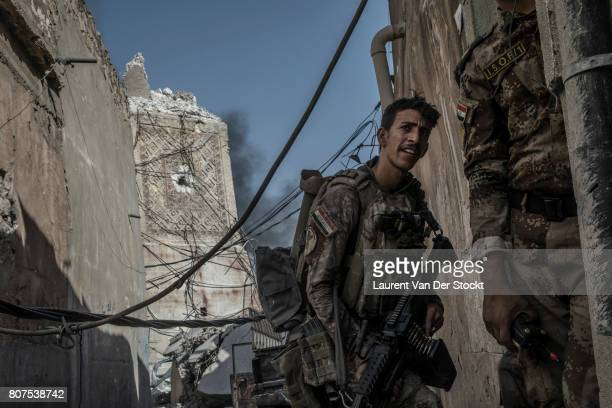 Iraqi soldiers pass the base of the destroyed Hadba minaret in alNuri mosque complex on June 29 in Mosul Iraq The Iraqi Army Special Operations...
