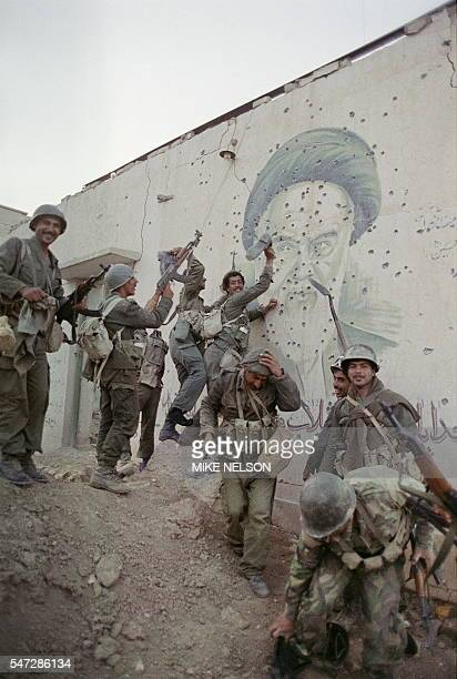 Iraqi soldiers pose 20 April 1988 in front of a huge bulletpocked mural of Iranian leader Ayatollah Khomeiny in the strategic Faw peninsula of...