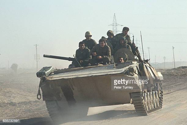 Iraqi soldiers ride on top of a BMP1 Infantry Combat Vehicle as they retreat from Kuwait