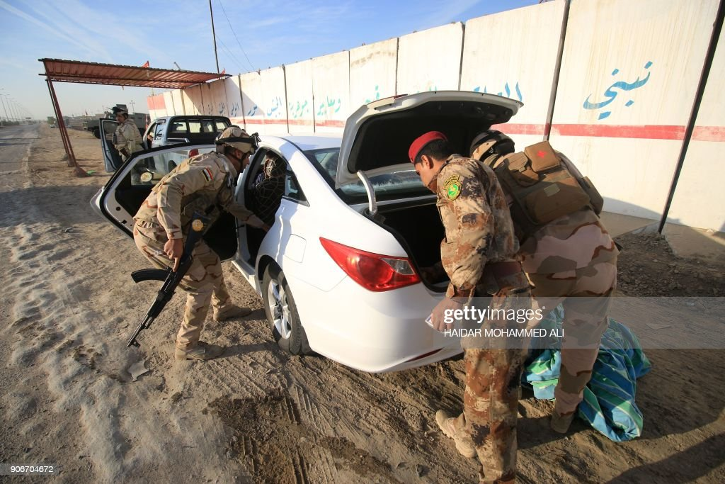 Iraqi soldiers search a vehicle as they control one of several ...