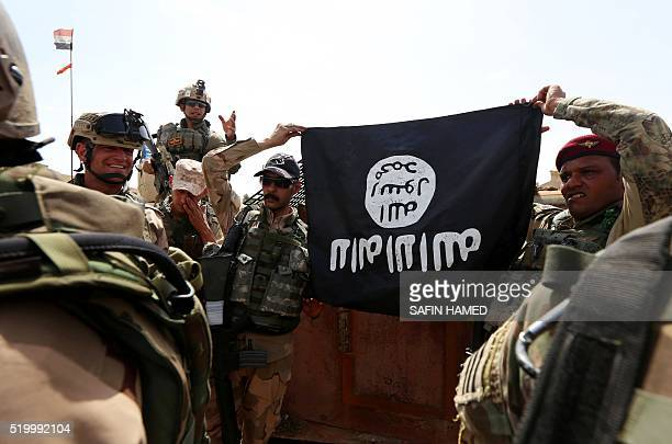 Iraqi soldiers show a flag that they seized from the Islamic State group as they hold a position near the frontline on April 9, 2016 in the town of...