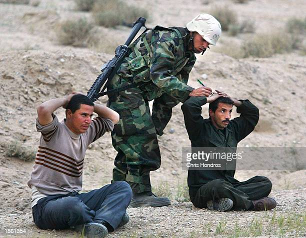 Iraqi soldiers sit on the ground while being processed after surrendering themselves and their troops to US Marines March 21 2003 in Safwan Iraq...