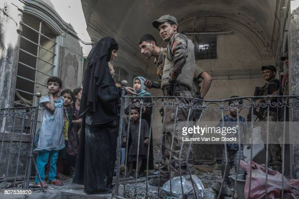 Iraqi soldiers speak to a family they discovered in alNuri mosque complex on June 29 in Mosul Iraq The Iraqi Army Special Operations Forces and...