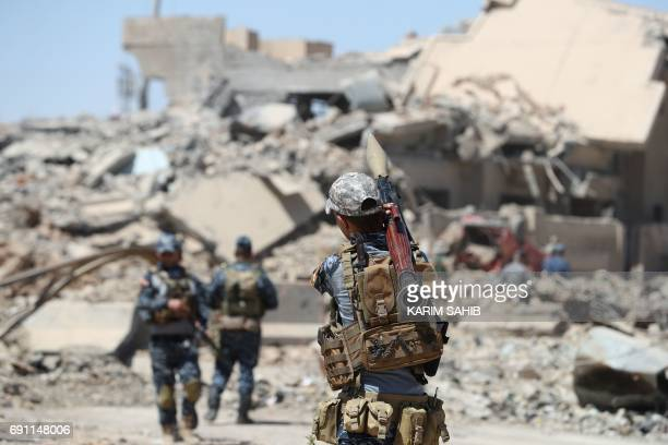 Iraqi soldiers stand at attention in western Mosul's Zanjili neighbourhood on June 1 2017 during ongoing battles between Iraqi forces to retake the...