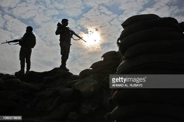 Iraqi soldiers stand guard near the Iraqi city of Qaim at the IraqiSyrian border on November 11 2018 Iraqi troops reinforced their positions along...