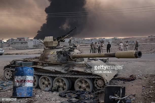 Iraqi soldiers stand next to a tank as smoke rises from the Qayyarah area some 60 kilometres south of Mosul on October 19 during an operation against...