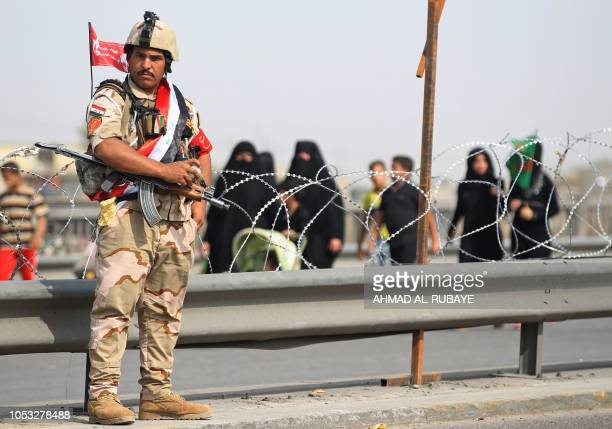 Iraqi soldiers stand on guard as they secure Shiite Muslim pilgrims walking on the outskirts of the Iraqi capital Baghdad towards the central Iraqi...