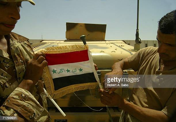 Iraqi soliders attach an Iraqi flag to the antenna on their Humvee June 20 2006 at the Muthana Airfield in central Baghdad Iraq When a number of...
