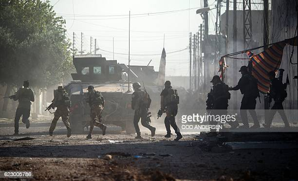 Iraqi Special Forces 2nd division soldiers come under fire from Islamic State group fighters while running across an intersection as they try to push...