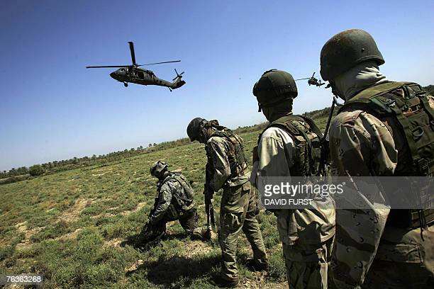 Iraqi special forces accompanied by US soldiers from 1501 ParaInfantry Regiment watch as a Blackhawk helicopter comes into land to transport them...