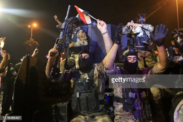 Iraqi special forces intervene to seperate clashing protesres and security forces during an anti-government demonstration in the Shiite shrine city...