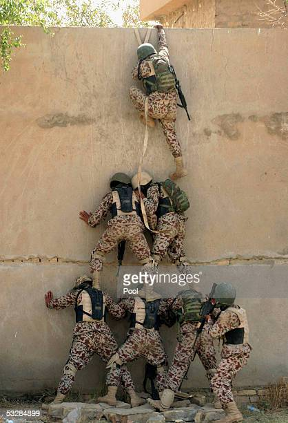 Iraqi special forces make a human pyramid to scale a wall while performing training exercises for Iraq's Prime Minister Ibrahim alJaafari and Iraqi...