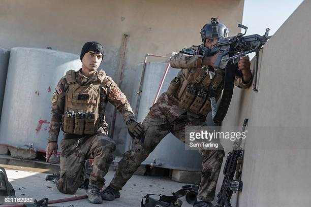 Iraqi Special forces soldiers fire at an ISIS sniper from the roof top in the neighborhood of Tahrir and Zahara, formerly named after Saddam Hussein,...