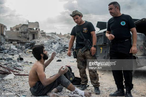 Iraqi Special Operation Forces soldiers interrogate a suspected Islamic State militant in the Old City district where heavy fighting continues on...