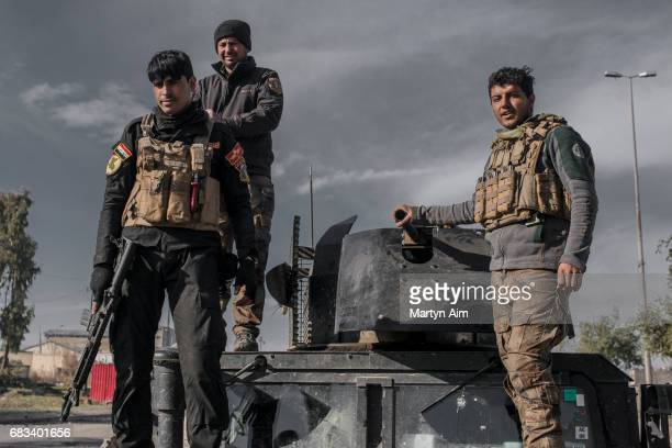Iraqi Special Operations Forces soldiers stand on top of their humvee in the liberated district of Al Jazaer in eastern Mosul recently recaptured...