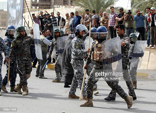 Iraqi special police members face demonstrators calling for jobs and better basic services at Baghdad's Tahrir square on March 11 2011 in the latest...