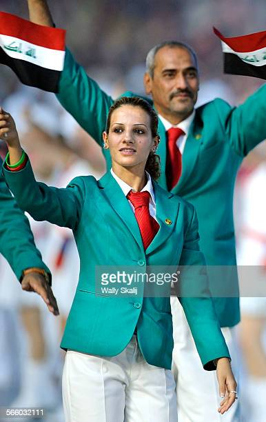 AUGUST 8TH 2008––Iraqi sprinter Dana Abdulrazak waves her countries flag during opening ceremonies in the 2008 Beijing Olympics