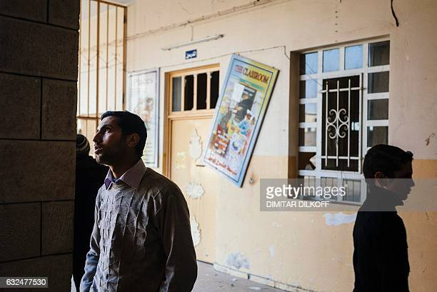 Iraqi students examine the damage at their school in Mosul's alZuhur neighbourhood on January 23 while scores of schools resumed their activities in...