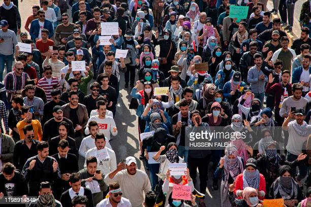 Iraqi students lifts placards as they march in an antigovernment protest in the southern city of Basra on February 6 after a night of violence blamed...