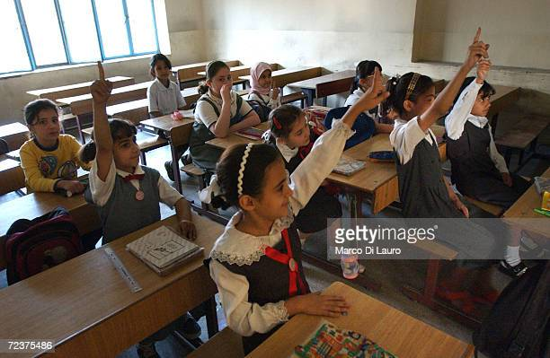 Iraqi students raise their hands to answer a teacher's question on the first day back to a Christian school May 3 2003 in Baghdad Iraq Approximately...