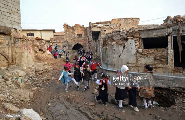 TOPSHOT Iraqi students walk through a damaged road on their way back from school in the northern city of Mosul on November 28 2018