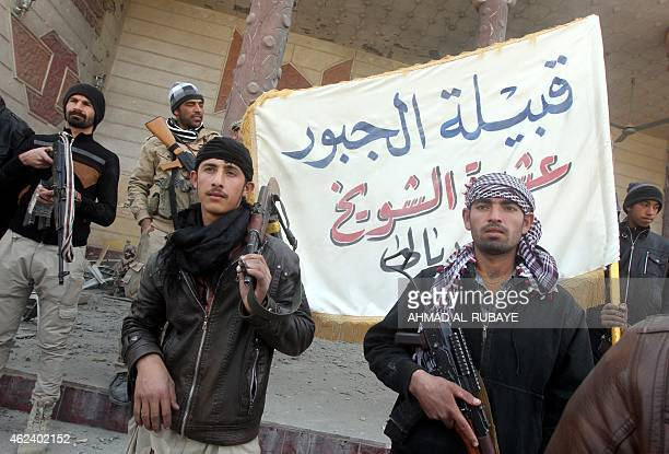 Iraqi Sunni fighters from the Jubur tribe hold a flag in front of a house that was damaged during clashes between the fighters and Islamic State...