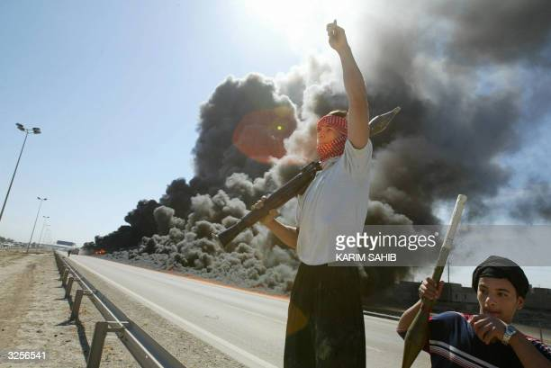 Iraqi Sunni Muslim insurgents celebrate in front of a burning US convoy they have attacked earlier 08 April 2004 in Abu Gharib on the outskirts of...