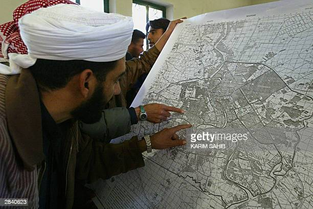 Iraqi Sunni Muslim men look at a map of Baghdad left behind by the US forces during the arrest of fundamentalist Imam Mahdi Ahmed Saleh alSumay at...