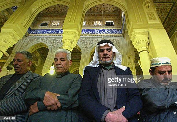Iraqi Sunni Muslim men perform the Friday noon prayer at the Ibn Taimiya mosque in the Yarmuk district of Baghdad 02 January 2004 US armoured...