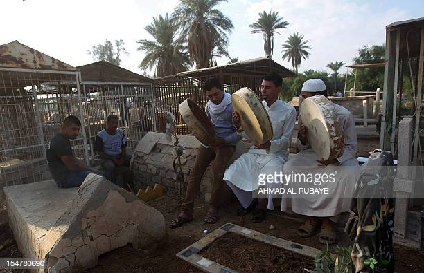 Iraqi Sunni Muslims perform religious rituals at the alGhazali cemetery in Baghdad on the first day of Eid alAdha on October 26 2012 Eid alAdha or...