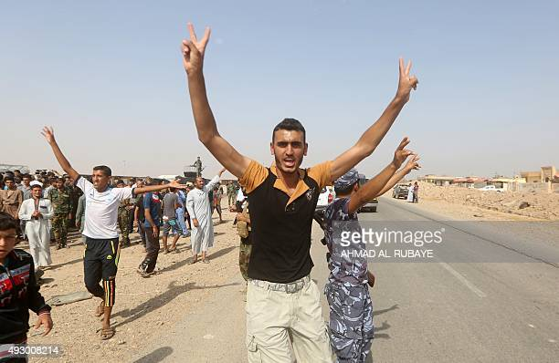 Iraqi Sunnis from the nearby village of Albu Tohme flash the sign of victory as they congratulate Shiite fighters from the Popular Mobilisation units...