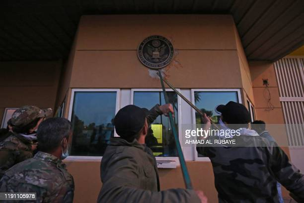 Iraqi supporters and members of the Hashed al-Shaabi military network pull off a plaque from the entrance of the US embassy in the capital Baghdad,...