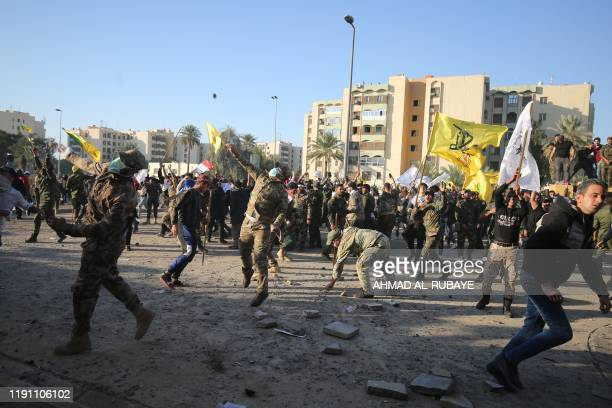 Iraqi supporters and members of the Hashed alShaabi military network hurl stones at the US diplomatic mission in the capital Baghdad on December 31...