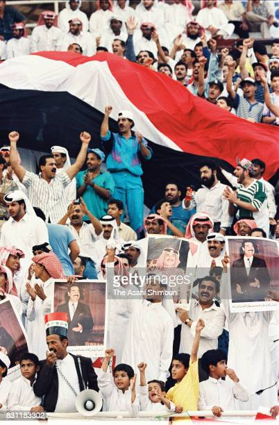 Iraqi supporters hold portraits of President Saddam Hussein during the FIFA World Cup Asian Final Qualifier match between Iraq and Iran at Khalifa...