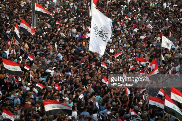 Iraqi supporters of cleric Moqtada alSadr wave their national flags and shout slogans during a demonstration in Tahrir Square central Baghdad on...