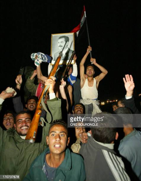 Iraqi supporters of exdictator Saddam Hussein rally in his support on a highway strech 50 kms north of Baghdad after the Qatarbased TV network...